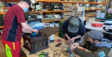 Unter Anleitung reparieren zwei Jugendliche einen Plattenspieler.